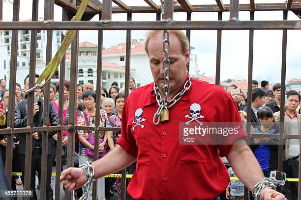 Canadian escape artist Dean Gunnarson performs cage escape over a lake on September 19 2014 in Zhangjiajie China