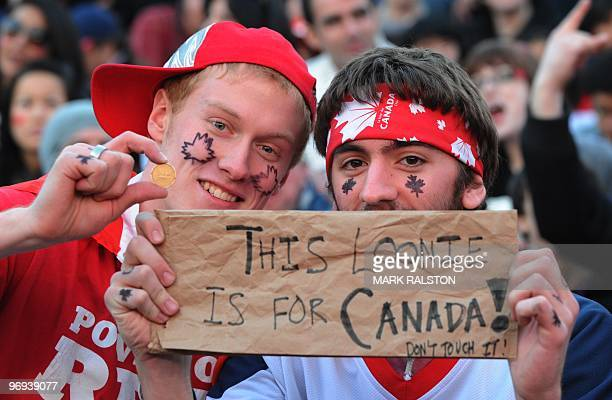 Canadian fans hold a dollar coin also called a 'Loonie' as they watch the US versus Canada Ice Hockey game on a giant TV during the Vancouver Winter...