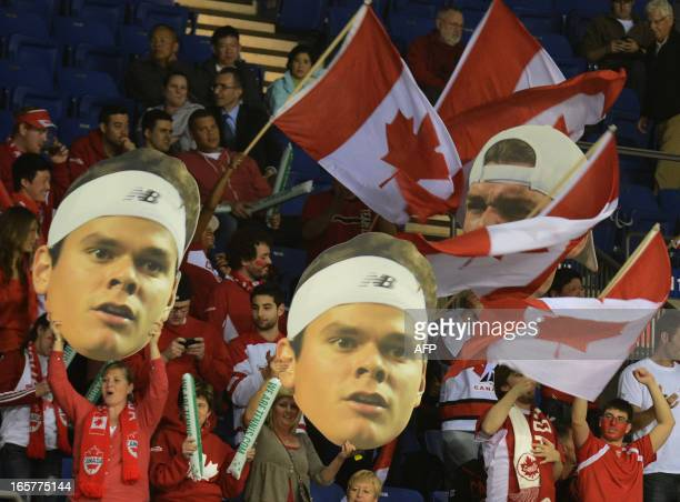Canadian fans hold poster-portraits of fellow Canadian Milos Raonic during his Davis Cup World Group quarter-final tie against Fabio Fognini of Italy...
