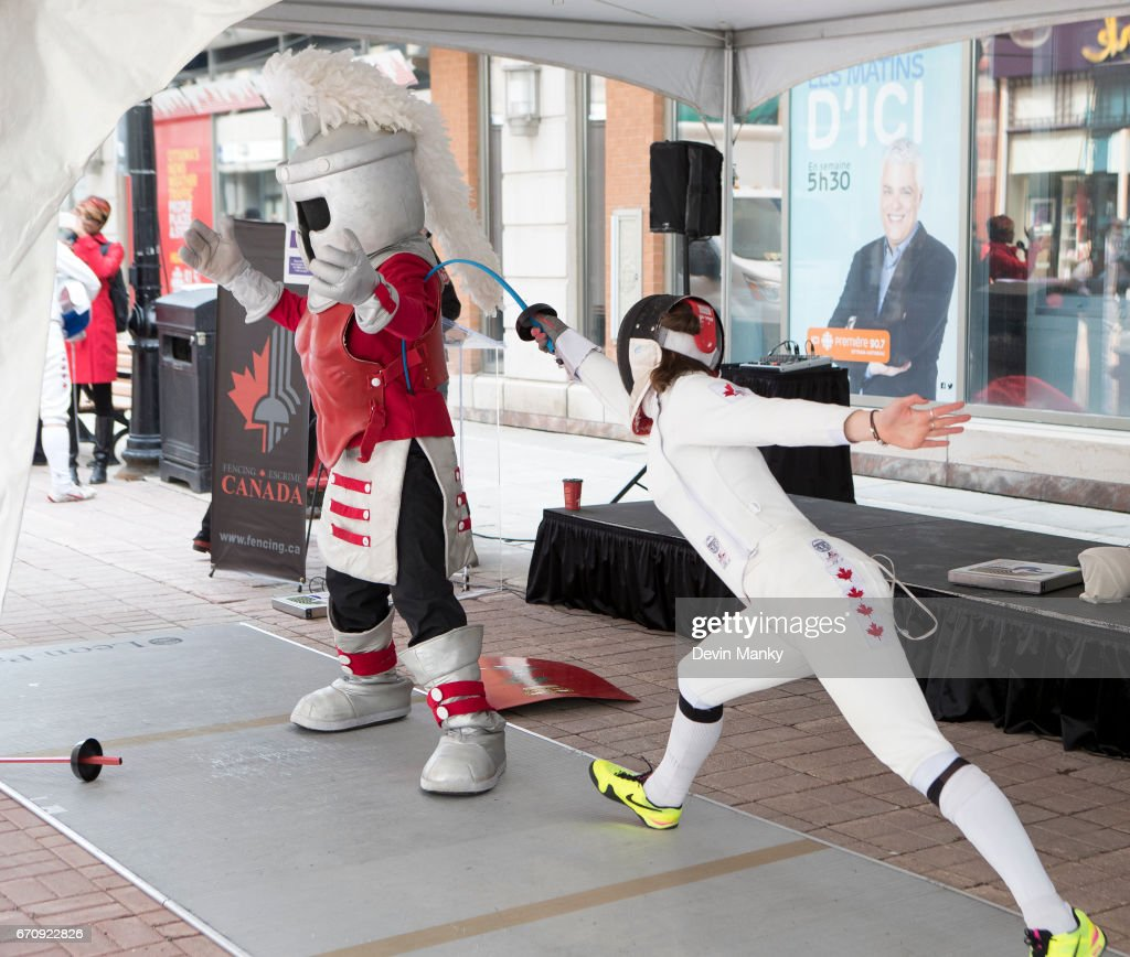 Canadian Fencing Olympian Leonora Mackinnon fences Paladin - the mascot for the Royal Canadian Military College during an outdoor fencing demonstration on Sparks Street during the Medley on the Street event on April 20, 2017 in Ottawa, Canada. The Medley on the Street event promotes Fencing Week in Canada and the upcoming National Canadian Fencing Championships.
