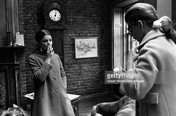 Canadian film and stage actress Genevieve Bujold smokes a cigarette as she stands with one hand in her coat pocket and listens to an unidentified...