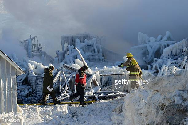 Canadian firefighters inspect the burnt remains of a retirement home in L'IsleVerte on January 23 2014 Firefighters searched the ashes of a Quebec...
