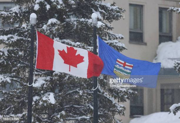 Canadian flag and an Alberta provincial flag fly outside The Fairmont Chateau Lake Louise hotel where an outdoor shinny hockey tournament is played...