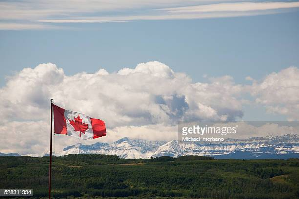 Canadian Flag Blowing In The Wind With Snowy Mountains In The Distance And Clouds With Blue Sky; Alberta Canada