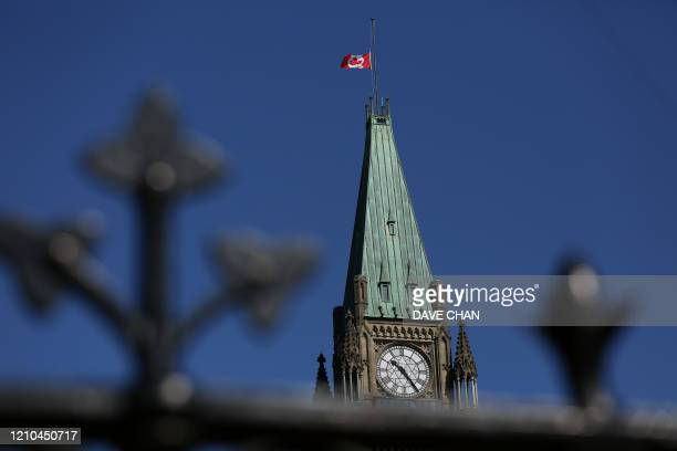 Canadian flag flies at half-mast on top of the Peace Tower to mourn the victims of the of the Nova Scotia shooting April 20, 2020 in Ottawa, Canada....