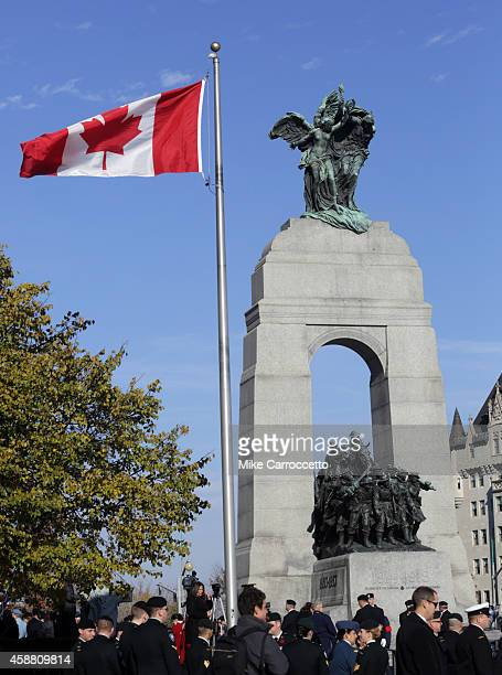 Canadian flag flutters in the breeze beside the National War Memorial Monument on Remembrance Day November 11 2014 in Ottawa Canada An estimated...