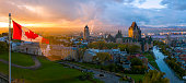Canadian flag flying over a picturesque Old Quebec City at sunset