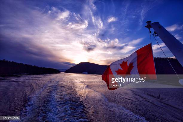 canadian flag waving at sunset at sea,vancouver,canada - canadian flag stock pictures, royalty-free photos & images