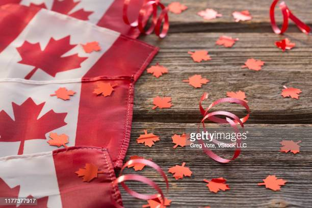 canadian flags and maple leaves on wood - canada day stock pictures, royalty-free photos & images