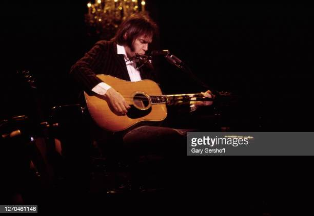Canadian Folk, Rock, and Pop musician Neil Young plays acoustic guitar and harmonica as he performs onstage at Nassau Coliseum, Uniondale, New York,...