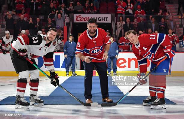 Canadian football player Laurent DuvernayTardif gets set to drop the ceremonial puck along with Brendan Gallagher of the Montreal Canadiens and...