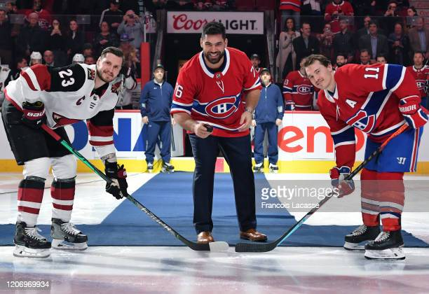 Canadian football player Laurent Duvernay-Tardif gets set to drop the ceremonial puck along with Brendan Gallagher of the Montreal Canadiens and...