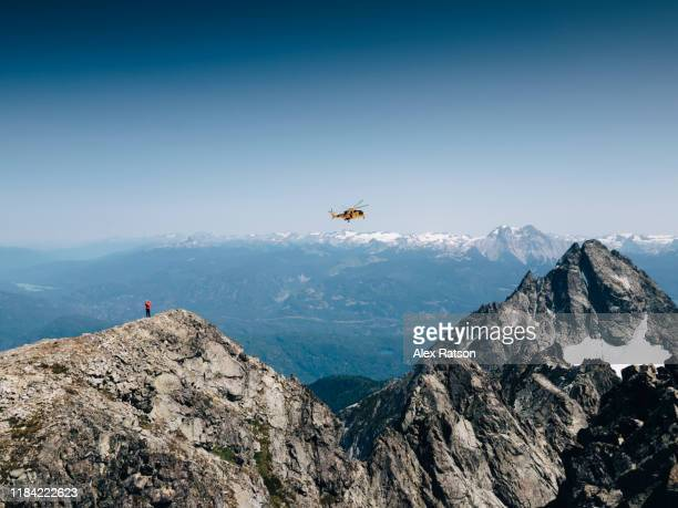 a canadian forces ch-149 cormorant fly's by the summit of a remote mountain with a mountain climber standing by - rescue stock pictures, royalty-free photos & images