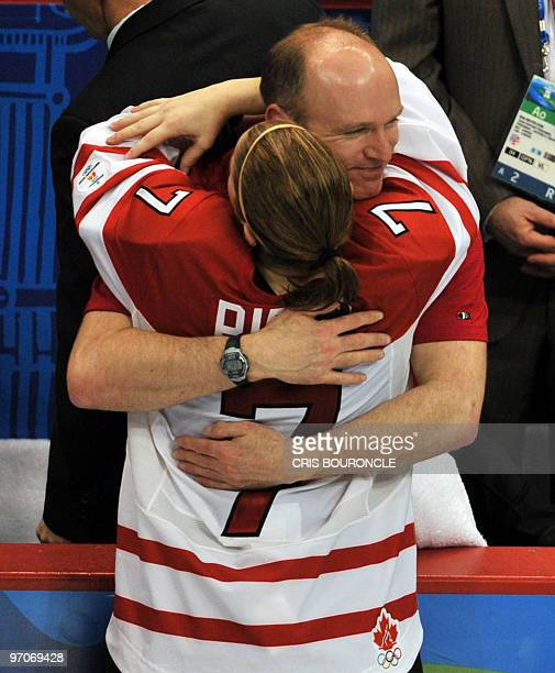 Canadian forward Cherie Piper gives a hug to her coach after team Canada received their gold medals during the medals ceremony in the Woman's Ice...