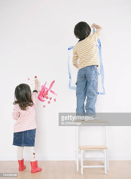 Canadian girl and boy drawing picture on wall in room