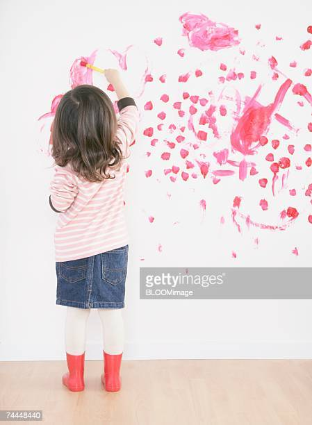Canadian girl drawing picture on wall in room
