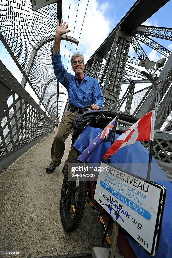 Canadian global walker Jean Beliveau pushes his three wheel stroller over the Sydney Harbour Bridge on June 6, 2010. a Canadian man who has spent the past decade walking around the world to promote peace crossed the Sydney Harbour Bridge on Sunday, having travelled 66,700 kilometres (41,354 miles) through 62 countries. A mid-life crisis prompted Jean Béliveau to begin his walk from Montreal, Canada in August 2000 and after thousands of days and nights on the road, he remains committed to his journey. AFP PHOTO / Greg WOOD
