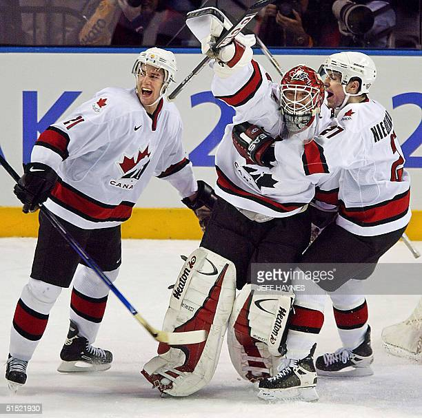 Canadian goalie Martin Brodeur celebrates with teammates Simon Gagne and Scott Niedermayer following their Men's Gold Medal Ice Hockey victory over...