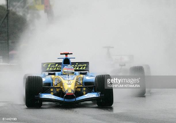 Canadian Grand Prix driver Jacques Villeneuve of Renault leads Finn Kimi Raikkonen of McLaren Mercedes in a wet-conditioned Suzuka circuit during the...