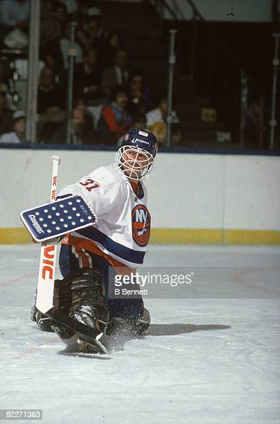 Canadian hockey player Billy Smith in the uniform of the New York Islanders slides on one knee after making a save during a game at Nassau Coliseum...