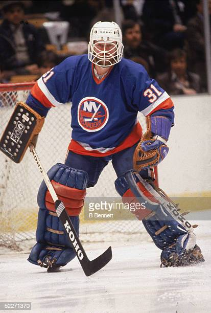 Canadian hockey player Billy Smith in the uniform of the New York Islanders, guards the net during a road game, 1980s.