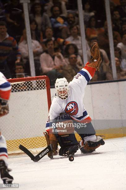Canadian hockey player Billy Smith in the uniform of the New York Islanders eyes the puck after making a save during a game at Nassau Coliseum...