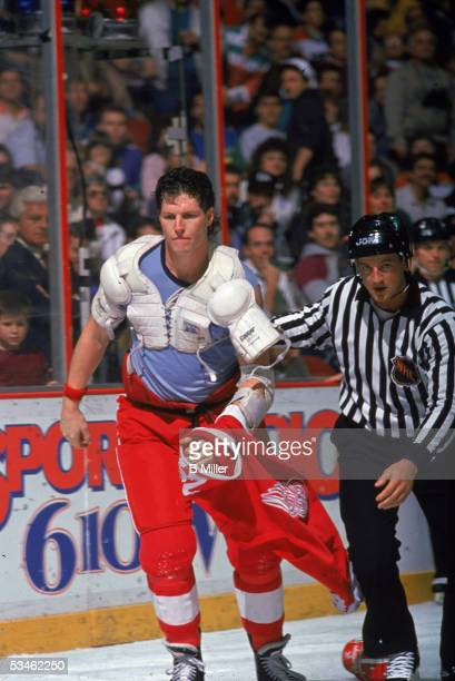 Canadian hockey player Bob Probert of the Detroit Red Wings jersey on his hand is escourted off the ice by an official after a fight at the Spectrum...