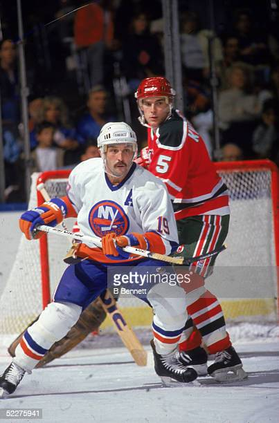 Canadian hockey player Bryan Trottier of the New York Islanders battles for position with Tom Kurvers of the New Jersey Devils during a game at...
