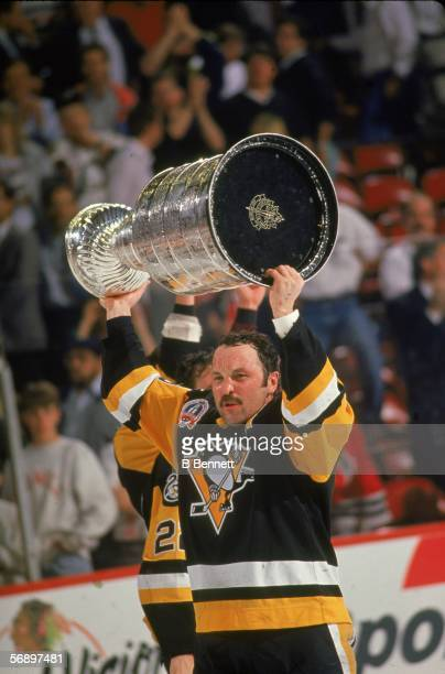 Canadian hockey player Bryan Trottier of the Pittsburgh Penguins raises the Stanley Cup over his head in celebration of their championship victory...