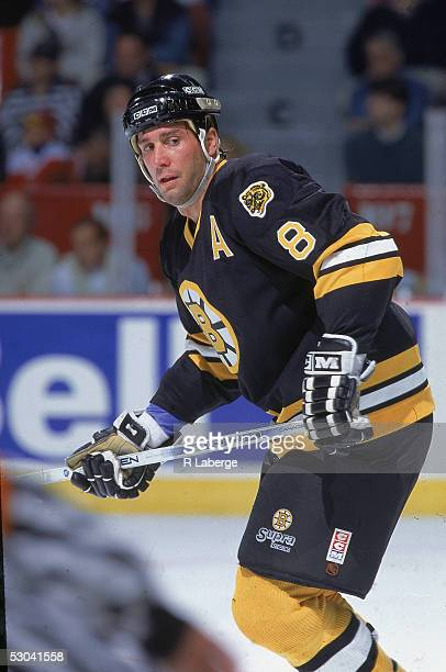 Canadian hockey player Cam Neely of the Boston Bruins glances behind him as he skates up the ice during a road game, 1990s.