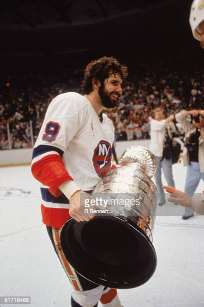 Canadian hockey player Clark Gillies forward for the New York Islanders holds the Stanley Cup on the ice after the Islanders defeated the...