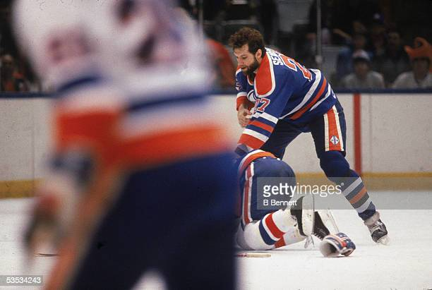 Canadian hockey player Dave Semenko of the Edmonton Oilers fights with an unidentified New York Islander who crawls on the ice on his hands an knees...