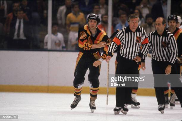 Canadian hockey player Dave 'Tiger' Williams of the Vancouver Canucks is escorted of the ice by two officials after a fight early 1980s