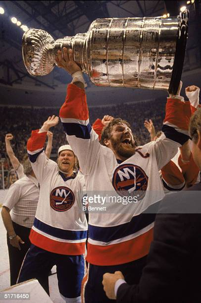 Canadian hockey player Denis Potvin, captain of the New York Islanders, holds the Stanley Cup in the air as the Islanders celebrate their first-ever...