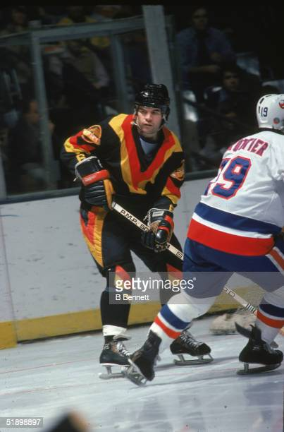 Canadian hockey player Dennis Kearns of the Vancouver Canucks keeps a close eye on the action as Bryan Trottier of the New York Islanders during a...