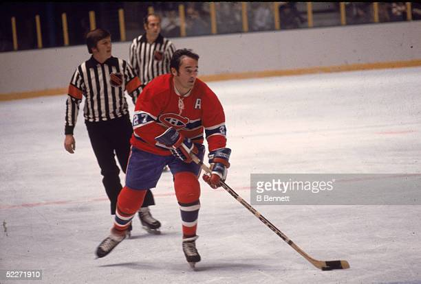 Canadian hockey player Frank Mahovlich of the Montreal Canadiens skates with the puck during a road game while several unidentified linesmen follow...
