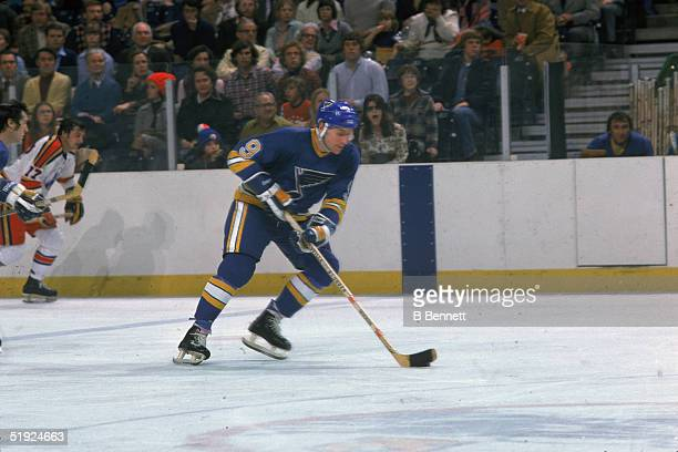Canadian hockey player Gordon 'Red' Berenson forward for the St Louis Blues skates the puck up the ice against the Scouts Kansas City Missouri...