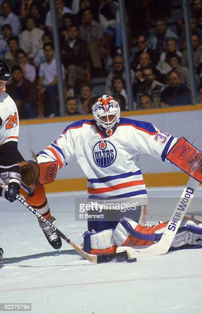 Canadian hockey player Grant Fuhr goalkeeper for the Edmonton Oilers makes a save while Derrick Smith of the Philadelphia Flyers during the Stanley...