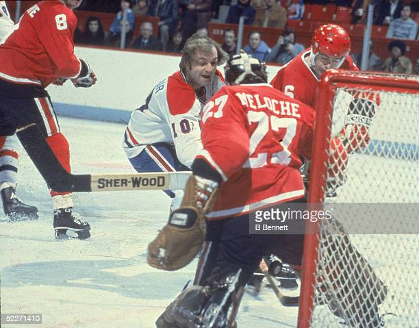 Canadian hockey player Guy Lafleur in the uniform of the Montreal Canadiens battles for the puck in front of the net as Cleveland Barons goalkeeper...