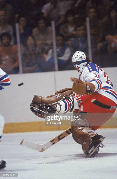Canadian hockey player John Davidson, goalkeeper for the New York Rangers, goes to the ice to make a save during a game at Madison Square Garden, New...