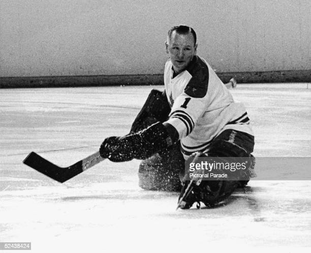 Canadian hockey player Johnny Bower goalkeeper for the Toronto Maple Leafs goes to the ice as he watches the puck 1960s