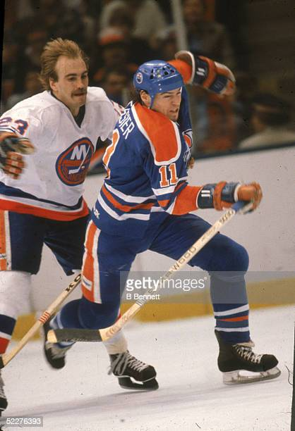 Canadian hockey player Mark Messier of the Edmonton Oilers skates past Bobby Nystrom of the New York Islanders during a game at Nassau Coliseum,...