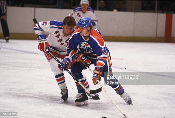 Canadian hockey player Mark Messier of the Edmonton Oilers struggles for position with Barry Beck of the New York Rangers early 1980s
