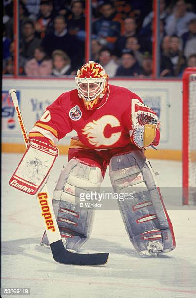 Canadian hockey player Mike Vernon of the Calgary Flames guards the net during a game, 1990s.