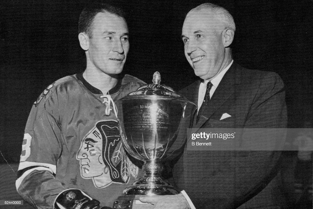 Canadian hockey player Pierre Pilote of the Chicago Black Hawks (left) is awarded the Norris Trophy for the National Hockey League's Outstanding Defenseman, 1964.