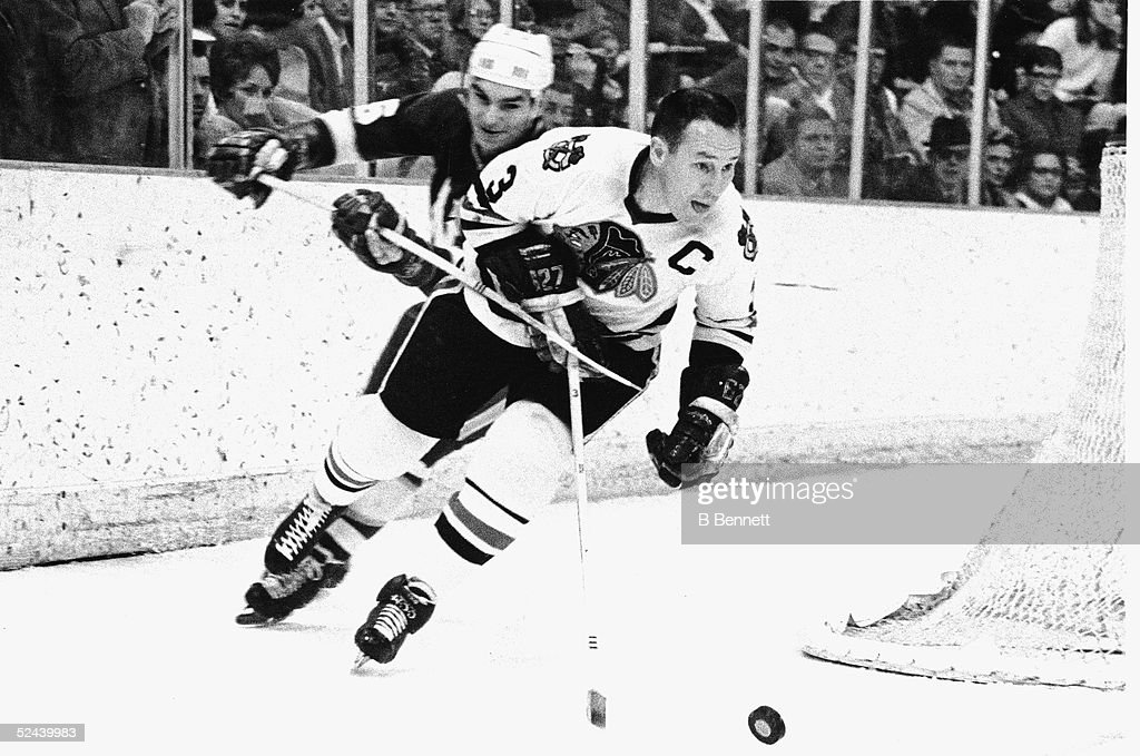 Canadian hockey player Pierre Pilote of the Chicago Black Hawks skates around the back of the net with the puck, followed closely by an unidentified Minnesota North Star, March 17, 1968.