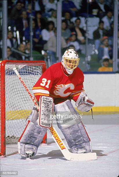 Canadian hockey player Rick Wamsley of the Calgary Flames guards the net during a game, late 1980s.