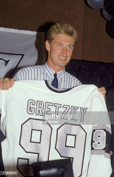 Canadian hockey player Wayne Gretzky holds up his new team jersey at a press conference after the announcement that he had been traded by the...