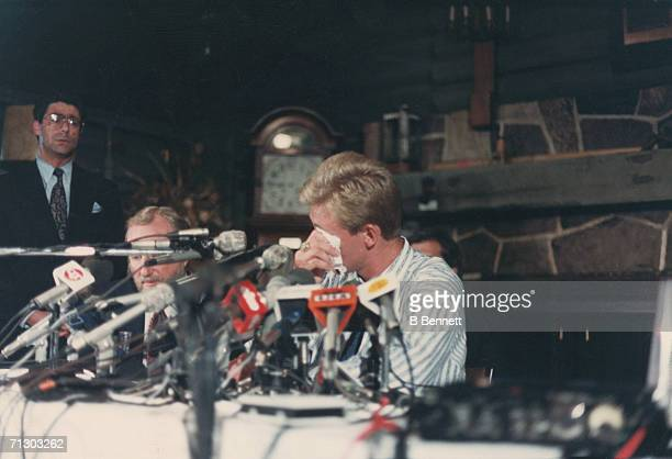 Canadian hockey player Wayne Gretzky sits behind a bank of microphones and dabs away tears at a press conference at the Edmonton's Petroleum Club...