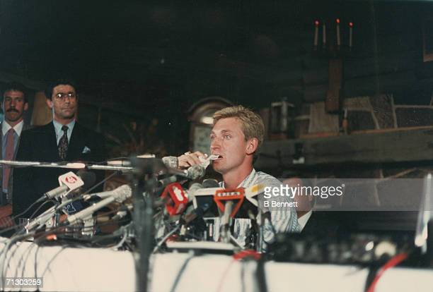 Canadian hockey player Wayne Gretzky sits behind a bank of microphones at a press conference at the Edmonton's Petroleum Club where it was announced...